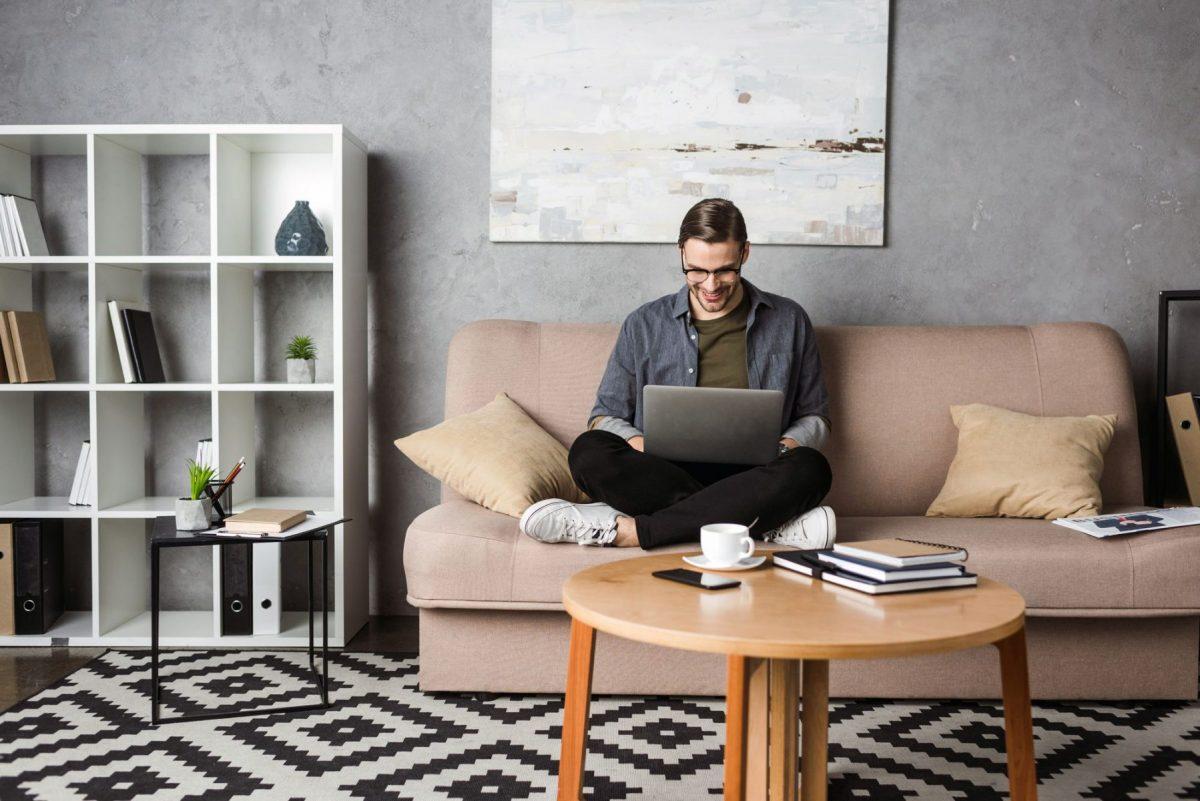homem sentado no sofá estudando com um notebook no colo